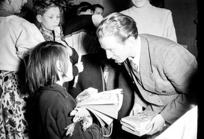 Kinderweihnachtsfest –kleines Mädchen bekommt ein Buchgeschenk überreicht, Foto 1954