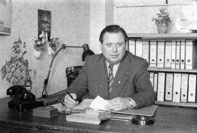 Mann mit Parteiabzeichen am Büroschreibtisch, Foto 1955