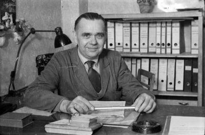 Mann im grauen Arbeitskittel am Büroschreibtisch, Foto 1955