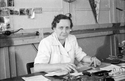 Frau in weißem Arbeitskittel an einem Büroschreibtisch, Foto 1955
