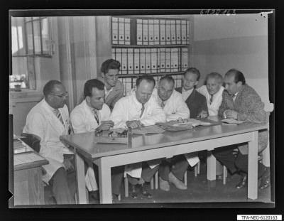 Arbeitsgemeinschaft/Brigade Kirschke (1. Mai), 8 Männer an einem Schreibtisch, Foto 1961