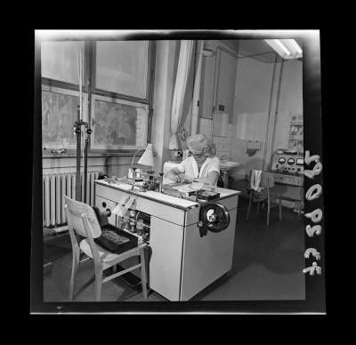 Arbeiterin am Arbeitsplatz in der Dioden Fertigung, Foto 1973, und Zeitzeugeninterview, 2019